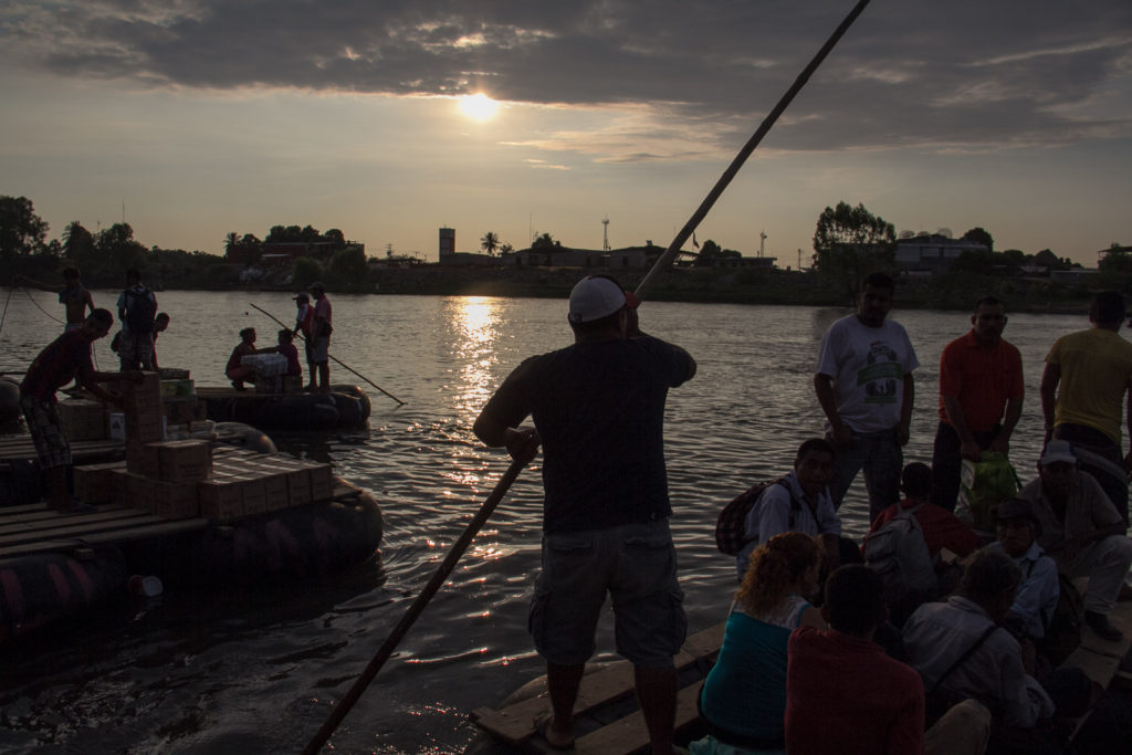 immigrants crossing the sachet river, a natural border between Mexico and Guatemala. boats are also used to traffic with merchandise.