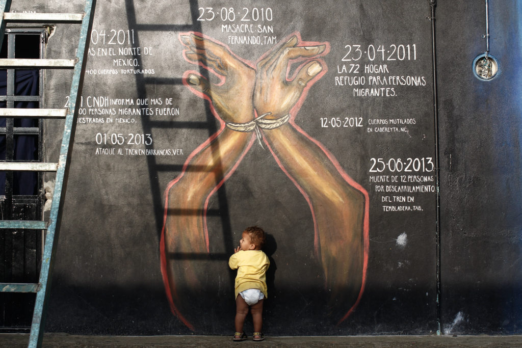 """A child walks around the facilities of the immigrant shelter """"La 72"""" a wall with dates of tragedies occurred to immigrants can be seen."""