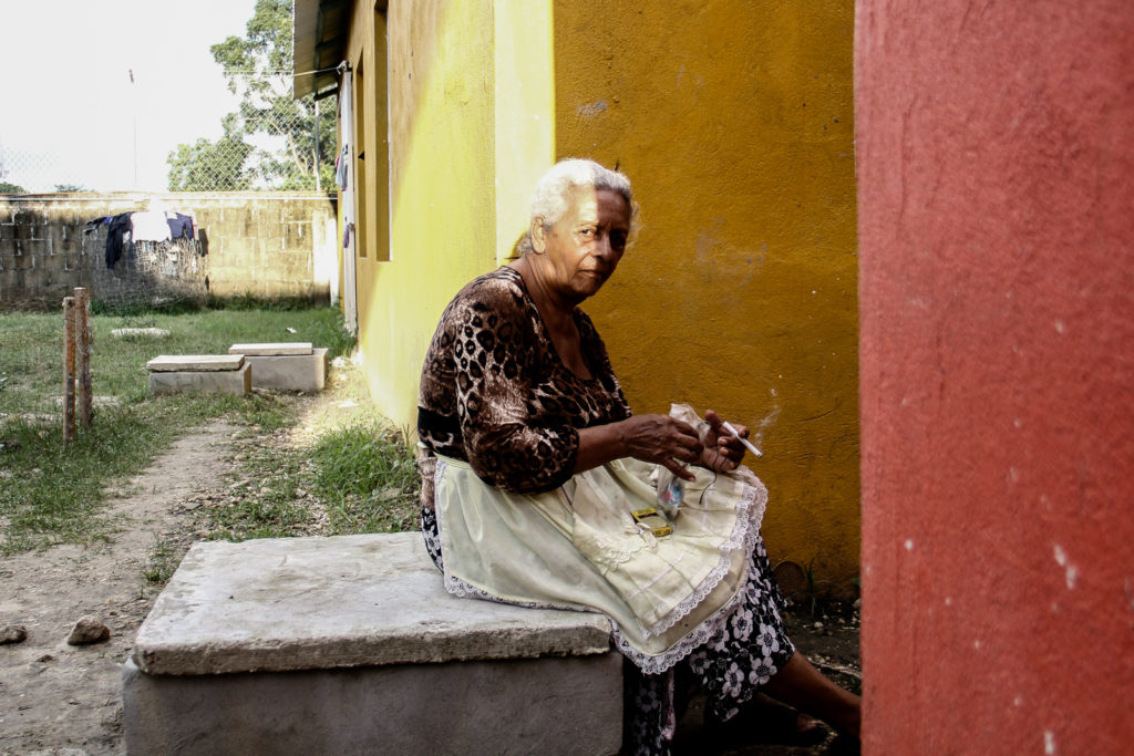 An old immigrant woman smokes a cigarette while she is making crafts to sell and get some money for the travel.