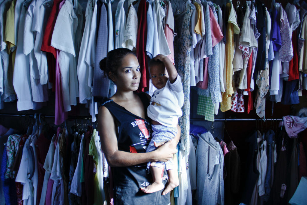 A 21 years old immigrant mother holds her child while she is looking for clothes to wear.