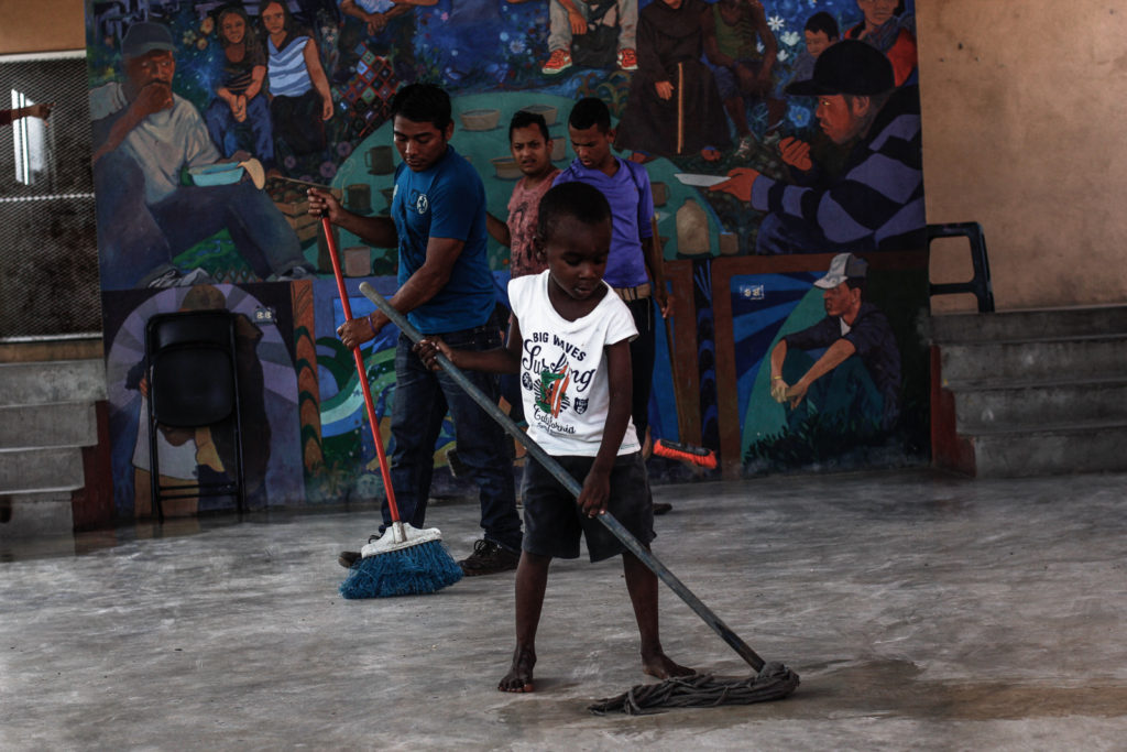 A immigrant child helps to clean the dining hall after being used