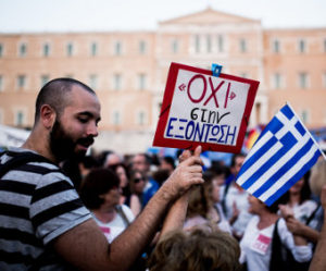 A protestor outside the Greek parliament building on 29 June 2015, holding a sign reading. By Jan Wellman.